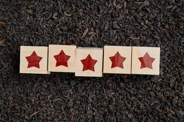 Il concetto di qualità del tè. stelle su cubi di legno.
