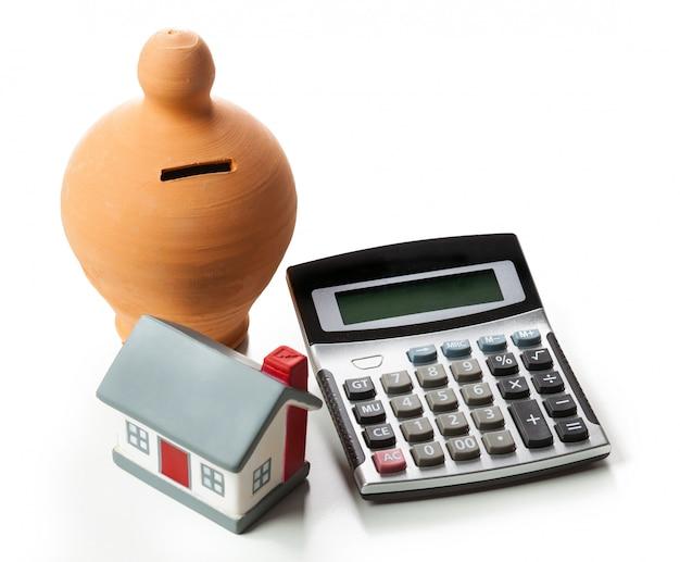 Il concetto di risparmio finanziario per comprare una casa. salvadanaio e calcolatrice.