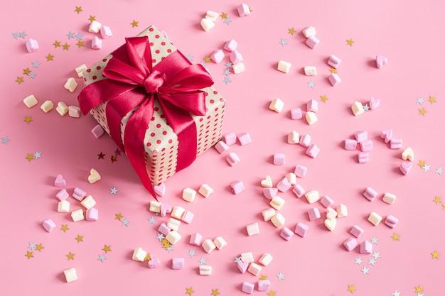 Il concetto di san valentino. confezione regalo con fiocco rosso su rosa.
