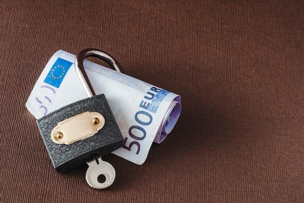Il concetto di sicurezza delle informazioni e servizi bancari. su uno sfondo marrone chiaro, un lucchetto aperto giace su un tubo arrotolato di una banconota da 500 euro.