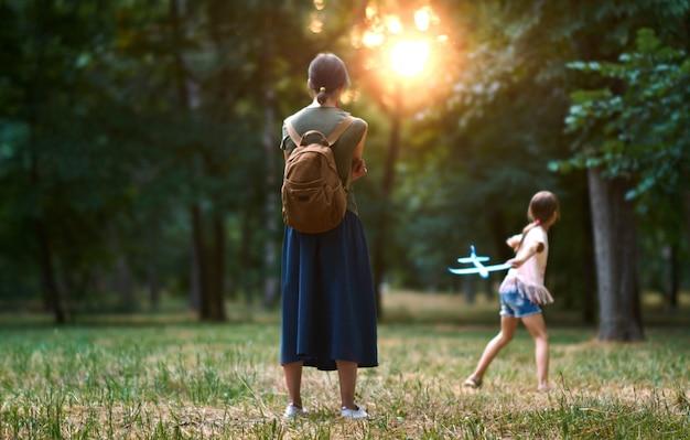 Il concetto di sogni e viaggi. ragazza felice del bambino con la madre che gioca con il giocattolo dell'aeroplano di estate sulla natura.