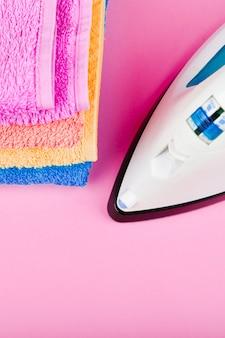 Il concetto di stirare i vestiti. ordine della casa. ferro e tessuto stirato. ferro da stiro elettrico su uno spazio rosa con asciugamani. asciugamani multicolori.