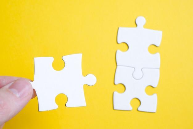 Il concetto di trovare una soluzione a un problema. un pezzo del puzzle è tenuto da un uomo con le dita accanto ad altri su una superficie gialla