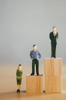 Il concetto di uguaglianza di genere, le figurine femminili in miniatura sono più basse delle figurine maschili