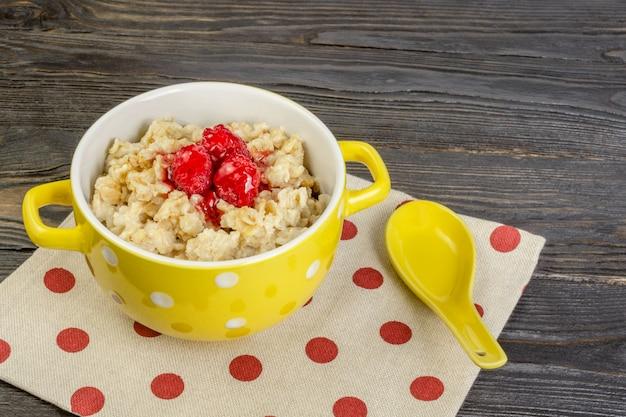 Il concetto di una dieta sana. faccia colazione con marmellata di farina d'avena e di lamponi in una ciotola gialla.