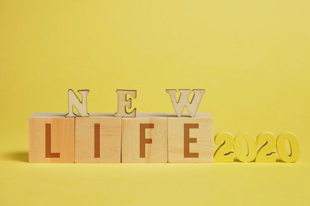 Il concetto di una nuova vita. numeri di legno 2020 accanto a cubi con lettere su uno sfondo giallo.