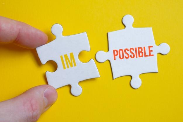 Il concetto è tutto è possibile. un pezzo del puzzle con l'iscrizione tiene le dita di un uomo accanto a un altro su una superficie gialla