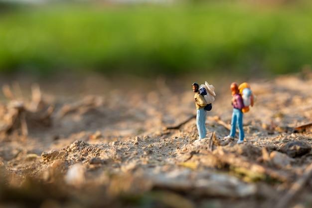 Il concetto miniatura della gente con la miniatura del viaggiatore con lo zaino sta e camminando sul prato