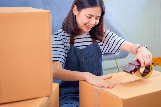 Il concetto startup di piccola impresa, il giovane proprietario asiatico della donna che lavora e che imballa sulla scatola al cliente al sofà in ministero degli interni, il venditore prepara la consegna.