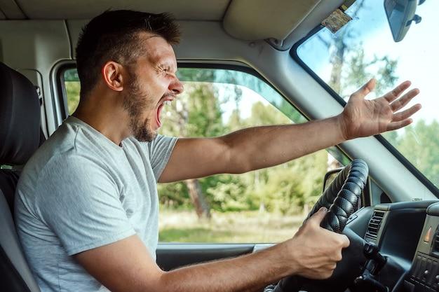 Il conducente dell'auto è indignato al volante durante il viaggio