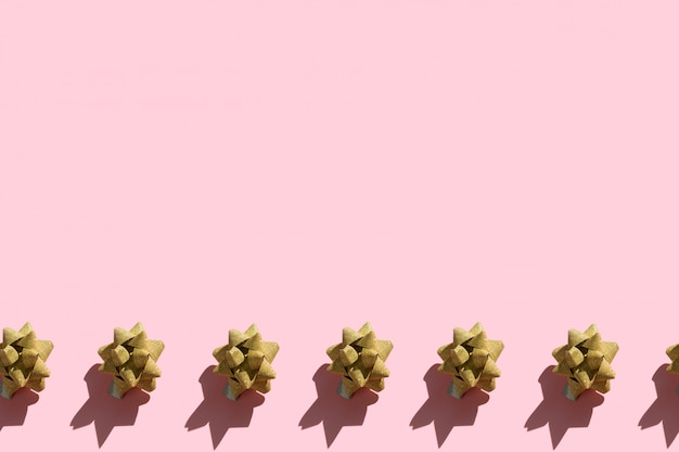 Il confine senza cuciture del nastro scintillante dell'oro si piega su un fondo di rosa pastello
