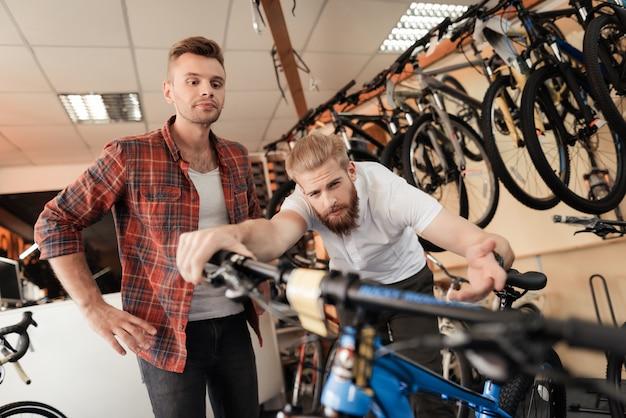 Il consulente mostra la bicicletta al cliente nel negozio di articoli sportivi.