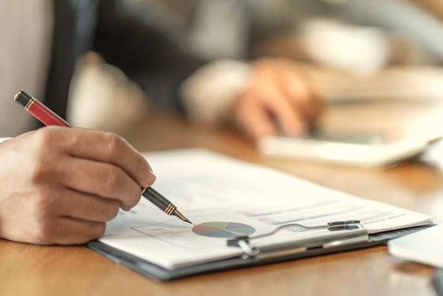 Il contabile che controlla i documenti relativi al grafico e al diagramma relativi all'informativa finanziaria e alla contabilità fiscale della società