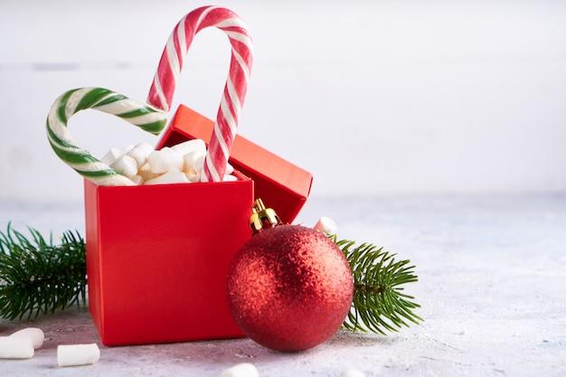 Il contenitore di regalo di natale con le caramelle gommosa e molle dolci e la caramella e l'abete si ramifica sul concetto leggero del fondo, di natale e del nuovo anno. copia spazio.