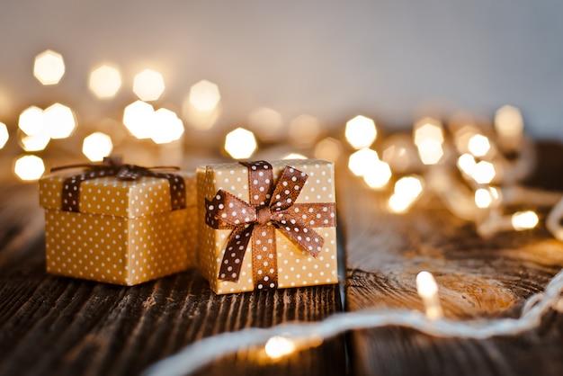 Il contenitore di regalo di natale giaceva su un tavolo di legno su un bokeh di luci festive.