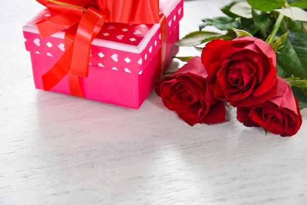 Il contenitore di regalo di rosa di concetto di amore del fiore del contenitore di regalo del giorno di biglietti di s. valentino con le rose rosse dell'arco del nastro fiorisce su di legno bianco