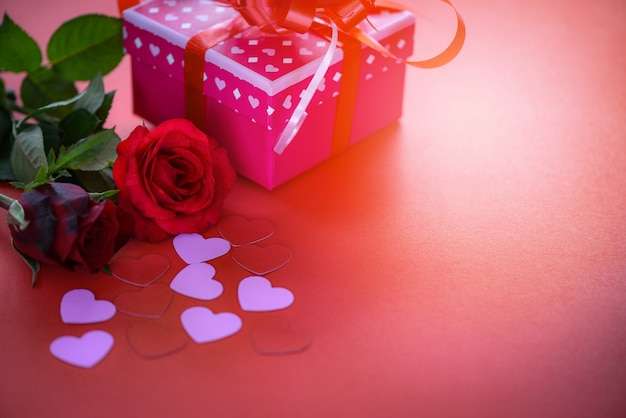 Il contenitore di regalo di rosa di concetto di amore del fiore del contenitore di regalo di giorno di biglietti di s. valentino con le rose di rosso dell'arco del nastro fiorisce e cuore rosa su rosso