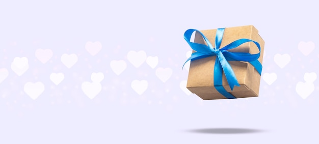 Il contenitore di regalo di volo su una superficie leggera con cuore ha modellato il bokeh. concetto di vacanza, regalo, vendita, matrimonio e compleanno. .