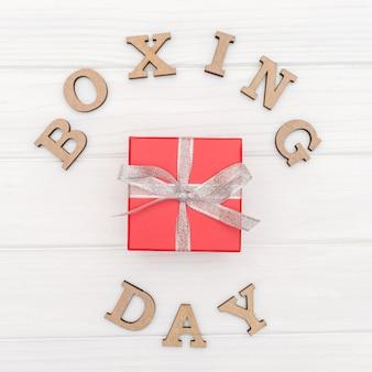 Il contenitore di regalo è legato con un nastro con le parole giorno di pugilato su fondo bianco di legno