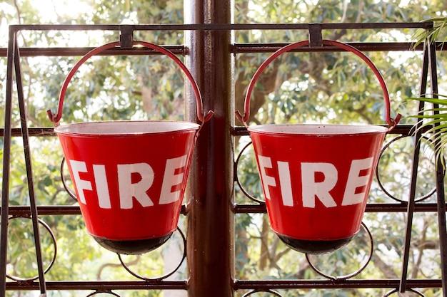 Il contenitore rosso del fuoco contiene la sabbia appesa a una griglia metallica