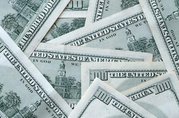 Il contesto astratto con molte centinaia di banconote in dollari si chiude su