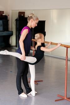 Il coreografo insegna al bambino le posizioni di balletto