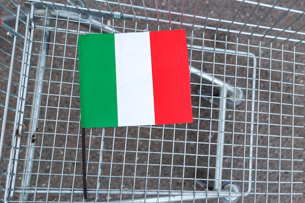 Il coronavirus in italia è il panico all'acquisto di cibo, la paura del coronavirus. focolaio di diffusione di coronavirus in italia. bandiera italiana nel carrello vuoto del supermercato. epidemia virale, romanzo coronavirus in europa ue