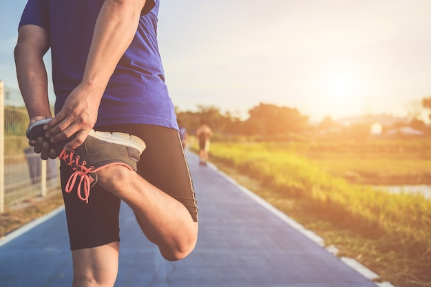 Il corridore asiatico riscalda il suo corpo prima di iniziare a correre su strada