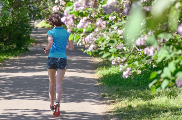 Il corridore della donna che pareggia nel parco di primavera con il fiore lilla, la mattina funziona all'aperto, la forma fisica ed eseguendo il concetto sano di stile di vita