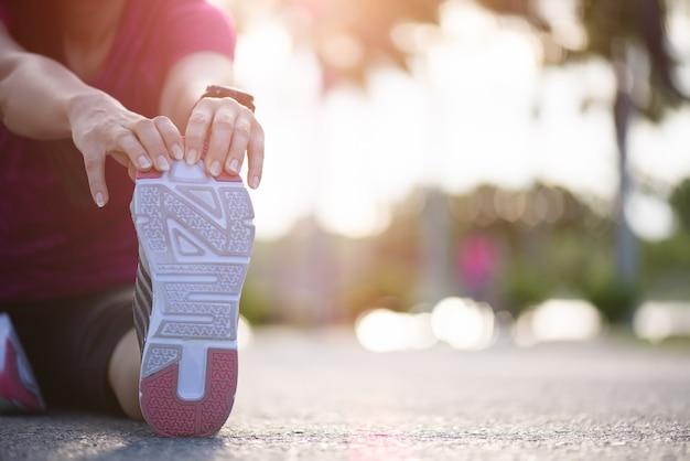 Il corridore della donna si siede sulla strada che allunga le gambe prima di correre nel parco. esercizio.