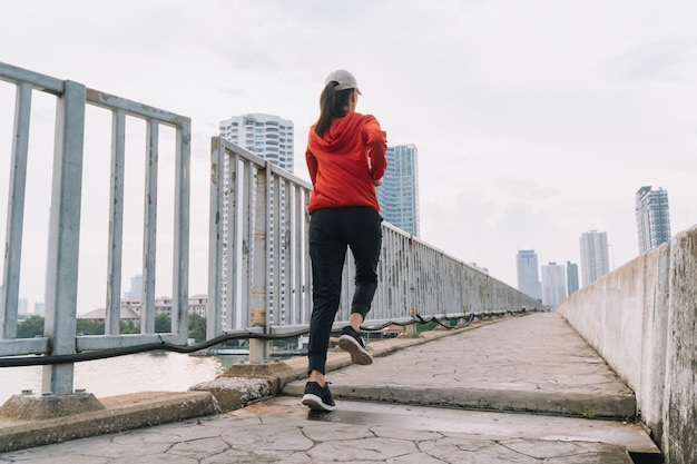 Il corridore delle giovani donne sulla strada sta correndo per esercitarsi sulla strada di città; concetto di sport, persone, esercizio fisico e stile di vita