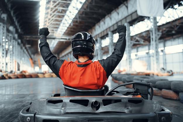 Il corridore di go kart ha alzato le mani