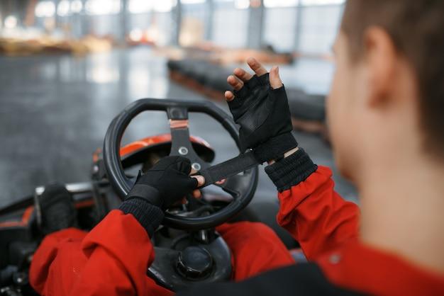 Il corridore di kart in uniforme rossa mette i guanti, sport automobilistico di kart al coperto.