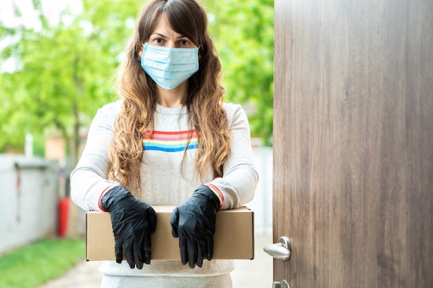 Il corriere femminile consegna un pacco a casa