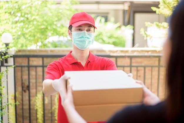 Il corriere in maschera protettiva e guanti consegna cibo in scatola durante lo scoppio del virus. consegna a domicilio sicura.