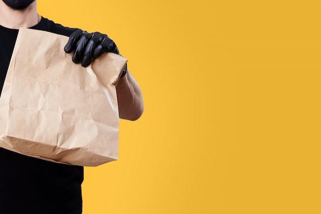 Il corriere in uniforme nera tiene il sacco di carta su fondo giallo