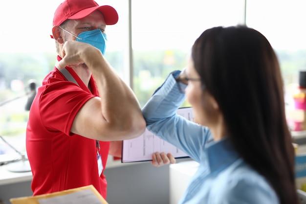 Il corriere maschio in maschera medica accoglie il cliente