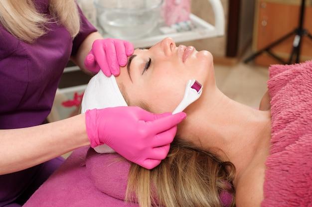 Il cosmetologo effettua il massaggio facciale con un rullo termostatico
