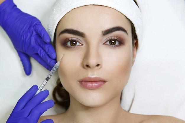 Il cosmetologo fa l'iniezione di bellezza nella faccia della donna nella clinica