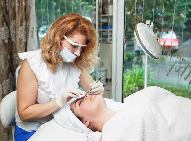 Il cosmetologo schiaccia l'acne sulla fronte del paziente con un ago medico