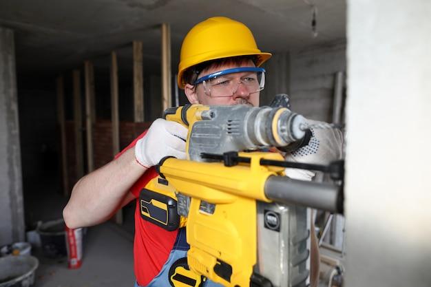 Il costruttore in casco tiene l'attrezzo pesante, perfora la parete