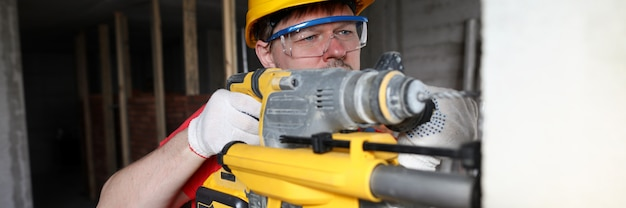 Il costruttore in casco tiene l'attrezzo pesante, perfora la parete.