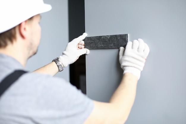 Il costruttore in guanti e casco sceglie il colore delle piastrelle per il muro dell'appartamento. l'uomo applica un campione di materiale da costruzione al muro