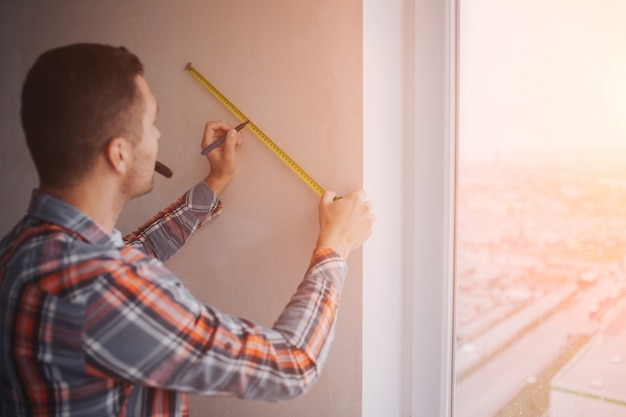 Il costruttore lavora al cantiere e misura la parete. il lavoratore in un casco arancione della costruzione fa le riparazioni nella casa
