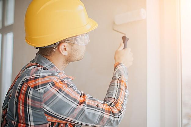 Il costruttore lavora in cantiere e misura il soffitto. un lavoratore in un casco arancione e un rullo di vernice dipinge il muro.