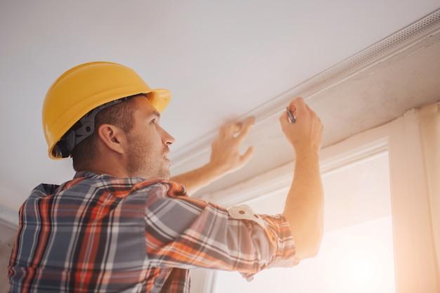 Il costruttore lavora nel cantiere e misura il soffitto. il lavoratore in un casco arancione della costruzione fa le riparazioni nella casa.