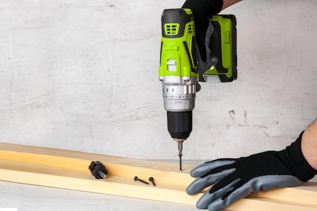 Il costruttore tiene in mano un cacciavite elettrico sullo sfondo di un muro di cemento. le viti si avvitano in una trave di legno. fai da te