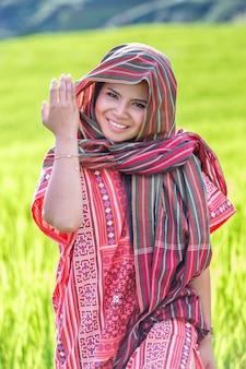 Il costume tradizionale di usura della bella donna asiatica del ritratto nell'azienda agricola del riso del terrazzo