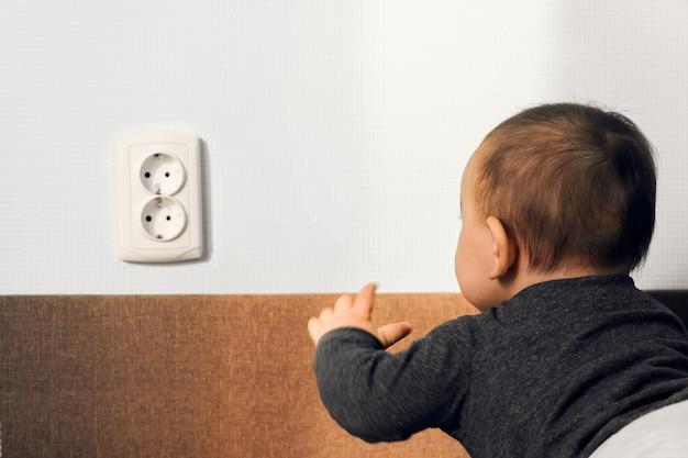 Il crawl del bambino ha messo il concetto della casa di sicurezza del pericolo di rischio della presa della parete del presa elettrica delle dita