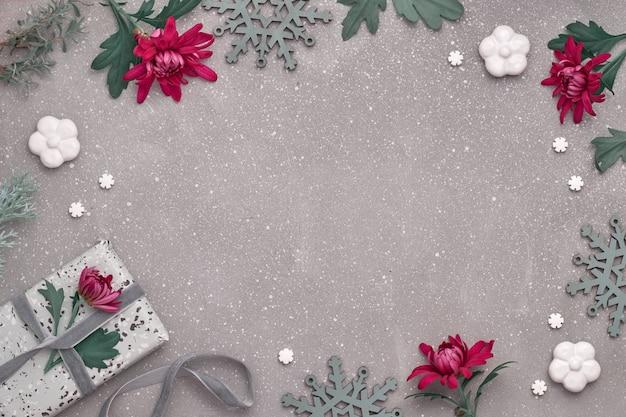 Il crisantemo di borgogna fiorisce sulla parete strutturata con le decorazioni dell'inverno, copia-spazio